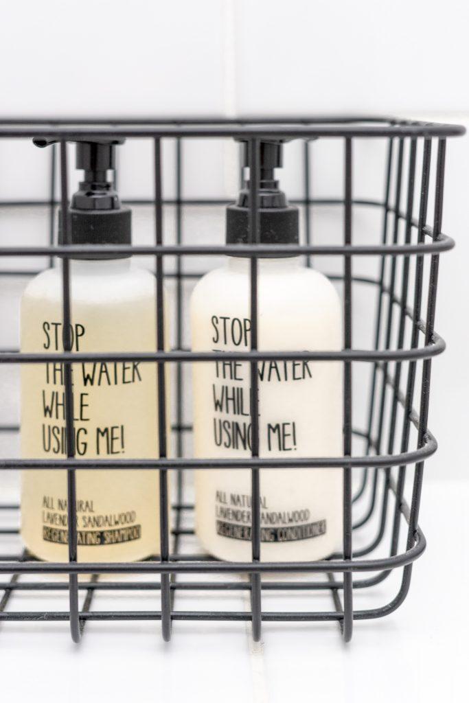Shampoo und Conditioner von Stopp Water While Using Me in schwarzem Drahtkorb von Granit