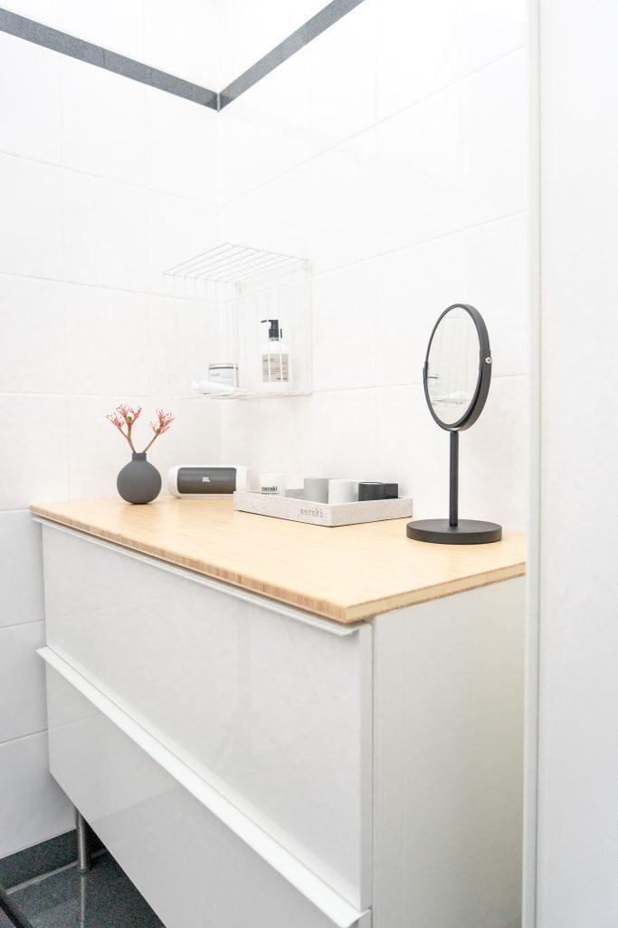 Badunterschrank Godmorgon von Ikea mit Gitterregal von Ib Laursen grauem Tablett von Meraki und Kosmetikspiegel in schwarz von Bloomingville
