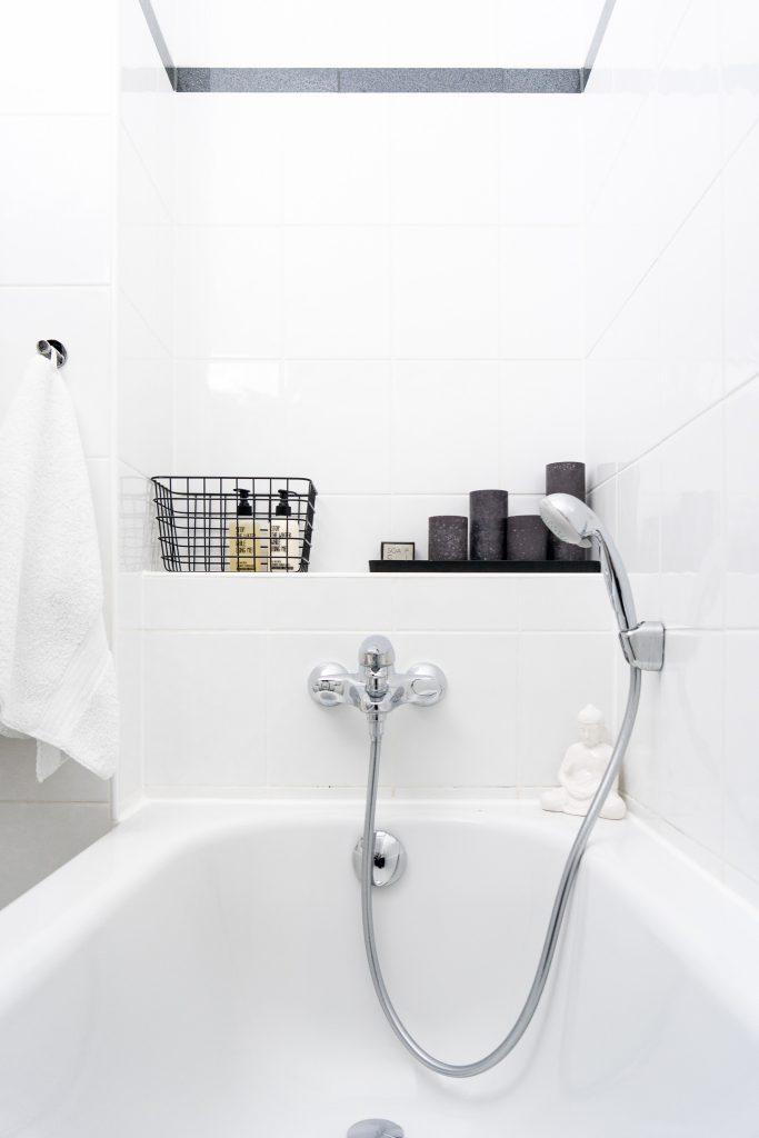 Badewanne mit Badaccessoires und schwarzen Kerzen
