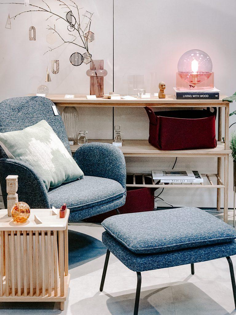 TrendSet Sommer 2019 Interior Trends Herbst und Winter 2019, blauer Sessel mit Hocker und Holzregal von Huebsch Interior