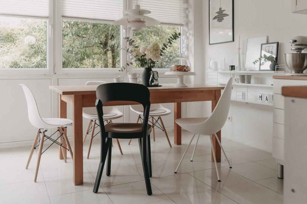 Verschiedene Stühle von Vitra, Thonet und Fritz Hansen am Esstisch mit PH5 Leuchte und Stringregal an der Wand