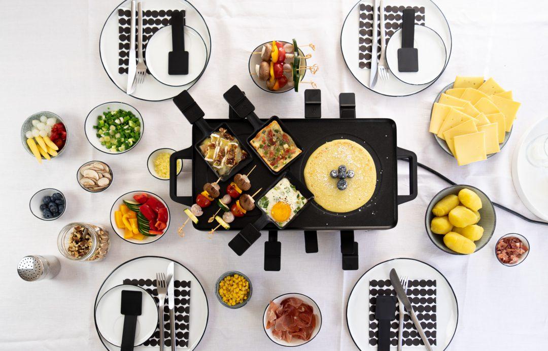 Raclette-gedeckter-Tisch-Zutaten-Crepes-Flammkuchen-Gemuesespiesschen-Spiegelei-Birne-mit Camembert-ueberbacken-Kartoffeln